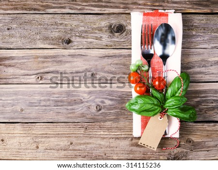 High Angle View of Spoon and Fork on Top of a Napkin Styled Tomatoes, Basil Leaves and Tag, Placed on Wooden Table with Copy Space for italian restaurant concept - stock photo