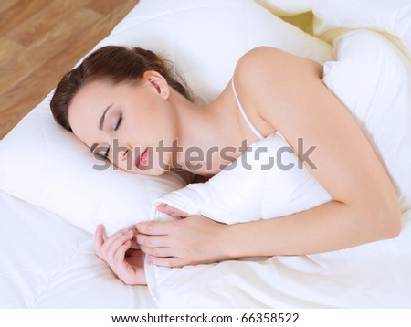 High angle view of the young sleeping woman on bed in bedroom - stock photo