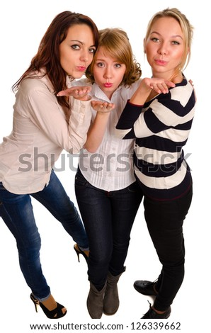 High angle view of three beautiful sexy young girls standing close together blowing a kiss isolated on white - stock photo