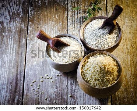 High angle view of three earthenware rustic pots containing dried bulgur and couscous made from crushed durum and semolina wheat and quinoa seeds, a high-protein staple of the goosefoot family - stock photo