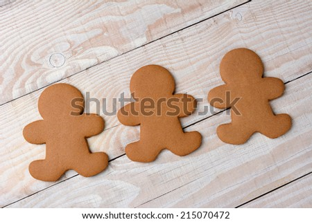 HIgh angle view of three gingerbread men on a rustic white kitchen table. The cookies are  plain and without icing. - stock photo