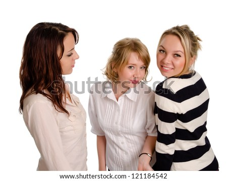 High angle view of three playful beautiful young woman in trendy modern outfits posing for the camera on a white studio background - stock photo