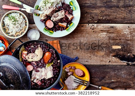 High Angle View of Traditional Brazilian Bean and Meat Dish Served with Side Plates and Garnishes on Rustic Wooden Table with Copy Space