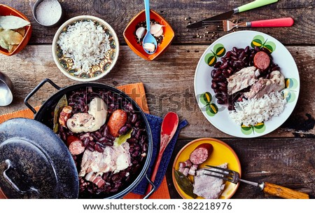 High Angle View of Traditional Brazilian Stew Made with Beans and Meats Served on Rustic Wooden Table with Side Plates, Rice and Garnishes
