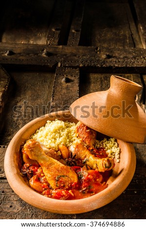 High Angle View of Traditional Tajine Berber Dish Made with Chicken Legs, Couscous and Savory Tomato Sauce Served in Covered Clay Pottery Dish on Rustic Wooden Decorative Table with Copy Space - stock photo