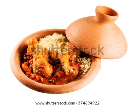 High Angle View of Traditional Tajine Berber Dish Made with Chicken Legs, Couscous and Savory Tomato Sauce Served in Covered Clay Pottery Dish on White Background with Copy Space - stock photo