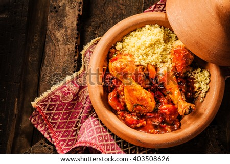 High Angle View of Traditional Tajine Berber Dish Made with Chicken Legs, Couscous and Savory Tomato Sauce Served in Covered Clay Pottery Dish on Decorative Wooden Table with Napkin - stock photo