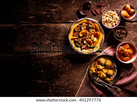 High Angle View of Traditional Tajine Dishes and Fresh Ingredients Served on Rustic Wooden Table with Cloth Napkin and Ample Copy Space - stock photo