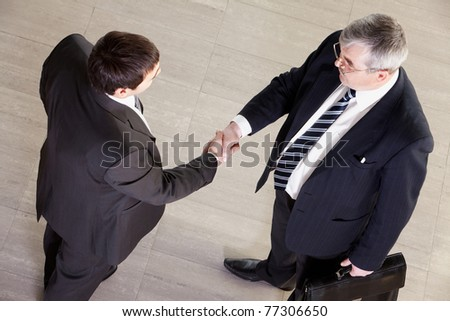 High angle view of two businessmen shaking hands - stock photo