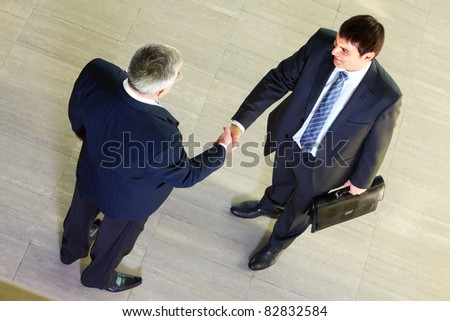 High angle view of two businessmen shaking hands after signing contract - stock photo