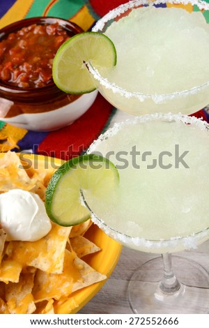 High angle view of two margarita cocktails for a Cinco de Mayo celebration. Surrounded by nacho chips and salsa on a bright Mexican table cloth. - stock photo