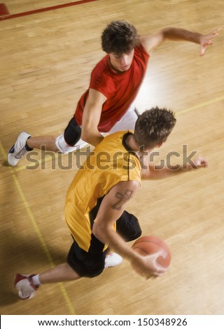 High angle view of two young men playing basketball on indoor court