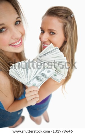 High-angle view of two young woman holding dollars against white background