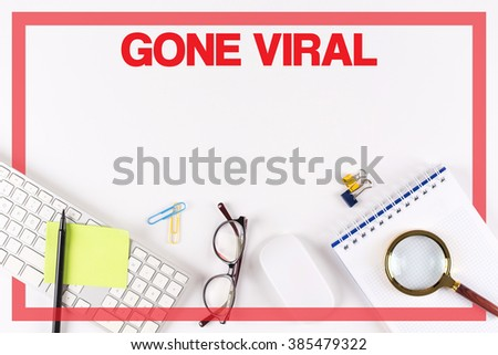 High Angle View of Various Office Supplies on Desk with a word GONE VIRAL - stock photo