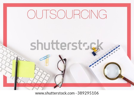 High angle view of various office supplies on desk with a word OUTSOURCING