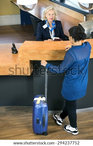 High angle view of woman with luggage standing at hotel reception desk - stock photo