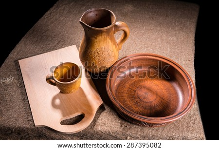 High Angle View of Wooden Handicraft - Carved Wood Pitcher, Bowl and Cup and Rustic Cutting Board on Burlap Covered Table Surface - stock photo