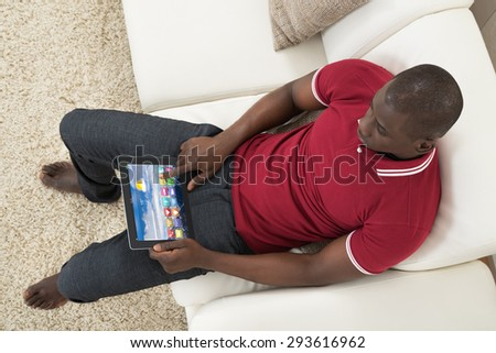 High Angle View Of Young African Man Sitting On Couch Using Digital Tablet - stock photo