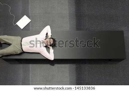 High angle view of young businessman relaxing on bench in office - stock photo