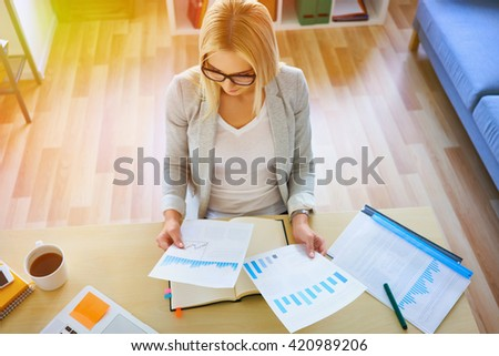 High angle view of young businesswoman working from home office with financial documents, notebook and laptop - stock photo