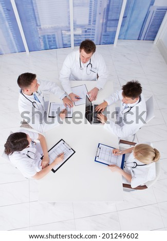 High angle view of young doctors having conference meeting in hospital - stock photo