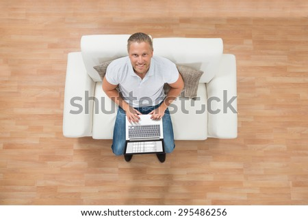 High Angle View Of Young Happy Man On Sofa Using Laptop - stock photo
