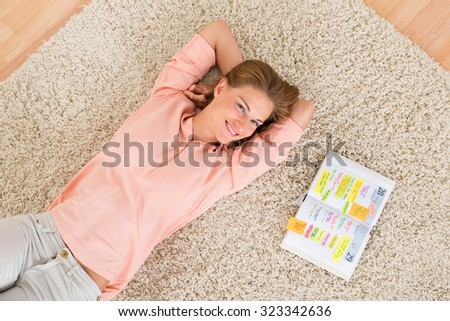 High Angle View Of Young Happy Woman With Diary Lying On Carpet - stock photo