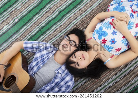 High angle view of young man playing guitar while lying on mat with his girlfriend - stock photo