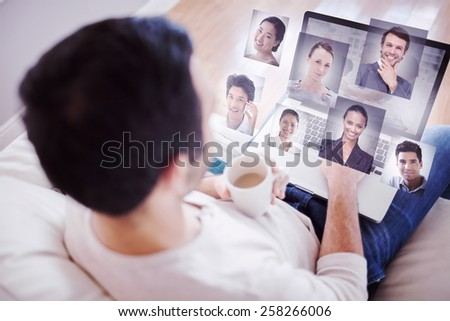High angle view of young man using his laptop against group of business people brainstorming together - stock photo