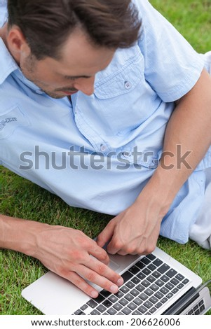 High angle view of young man using laptop in park - stock photo