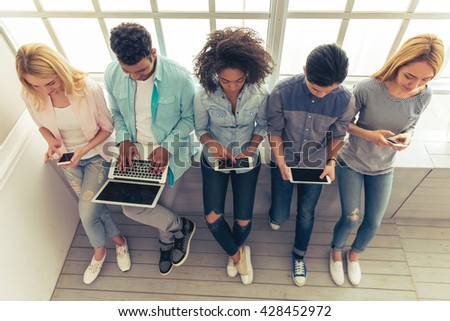 High angle view of young people of different nationalities using gadgets