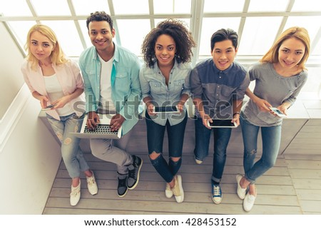 High angle view of young people of different nationalities using gadgets, looking at camera and smiling - stock photo