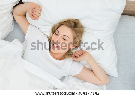 High Angle View Of Young Woman Stretching Arms In Bed
