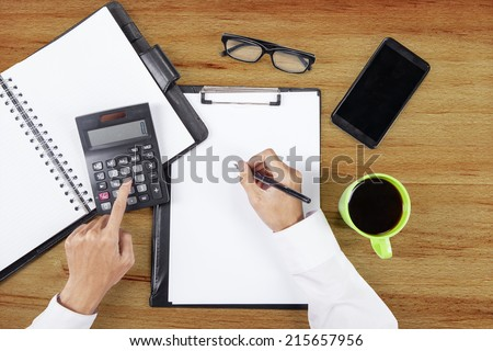 High angle view table of hands using calculator and writing on paper - stock photo