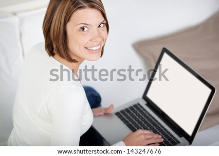 High angle view to the blank white screen of a smiling young woman with a laptop - stock photo