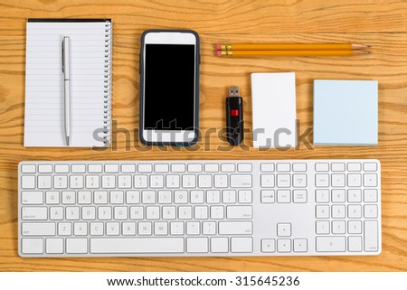 High angled view of a highly organized desktop consisting of computer keyboard, pencils, pen, cell phone, notepad, business cards and thumb drive. Horizontal layout.