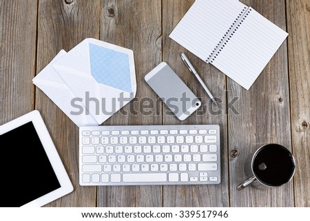 High angled view of working desktop with cell phone, pen, paper, computer keyboard, coffee, envelopes, laptop and coffee. Concept of integrating tradition with modern technology.   - stock photo