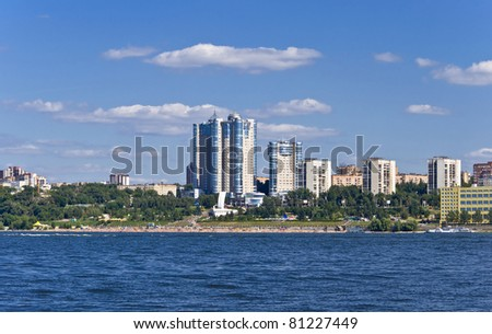 High apartment buildings on the quay. Beach filled with people. Summer urban landscape with a river. Samara. Russia.