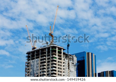 high buildings under construction with cranes at evening