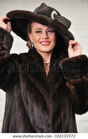 High class modern woman dressed in luxurious fur coat and fur hat - stock photo