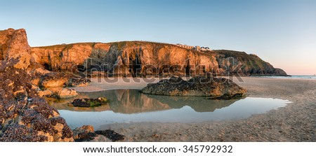 High cliffs and rock pools at low tide on Perranporth beach on the Cornwall coast - stock photo