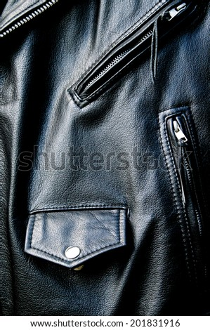 High contrast close up of black leather biker jacket showing zippered pockets and coin pocket with snap button and portion of belt in sunshine. - stock photo