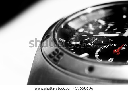 High contrast image of a men's wristwatch close up, black and white with red hads.
