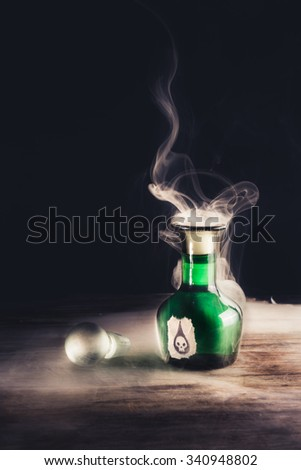 high contrast image of a poison bottle on a wooden surface - stock photo
