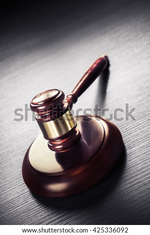 high contrast image of Judge gavel on a black wooden background - stock photo