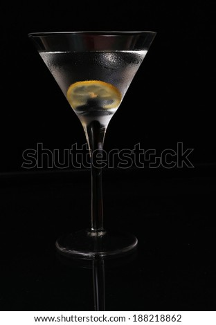 High contrast image of martini in chilled glass with lemon twist on black background with light shining through the drink.  Vertical Format with Copy Space - stock photo