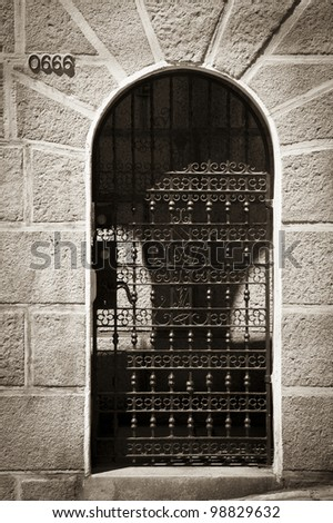 High contrast old metal door gate with many details in sepia tone surrounded by a stone wall