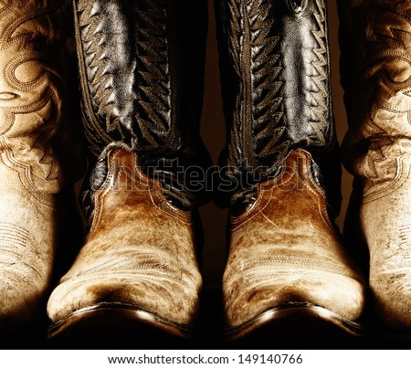 High contrast photo of several pair of worn cowboy boots, with center pair being a matched pair.