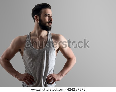 High contrast portrait of young fit bearded man with hands on hips looking away with copyspace over gray background