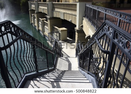 High Contrast Wrought Iron stair well leading to a platform overlooking water and fountains